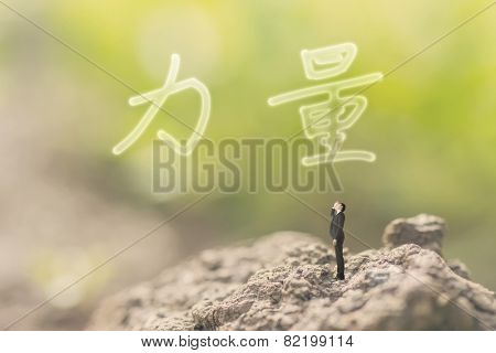 one person stand in the outdoor and looking up the Chinese text(mean power) on nature background, concept of power, strength, force.
