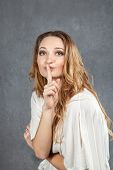 stock photo of hush  - Attractive young woman with finger on lips concept of student show quiet silence secret gesture hush - JPG