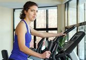 stock photo of elliptical  - Young positive woman doing exercises with elliptical trainer in gym - JPG
