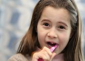 foto of teeth  - pretty girl without a tooth while brushing teeth in the bathroom - JPG
