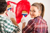 picture of mischief  - Young happy couple are painting a heart on the wall while doing repair at home - JPG
