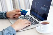 pic of plastic money  - man doing online shopping with credit card on laptop - JPG