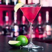 stock photo of cosmopolitan  - cosmopolitan cocktail in front blurred bottles of alcoholic drinks in the background.