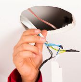 foto of electrician  - Electrician assembling power supply for ceiling illumination - JPG