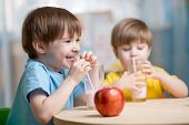 stock photo of kindergarten  - kids drinking milk at home at home or kindergarten - JPG