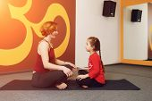 pic of om  - Mother and child yoga practice on the background of the Indian symbol of OM - JPG