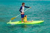 picture of paddling  - Father and his adorable little daughter paddling on stand up board having fun during summer beach vacation - JPG