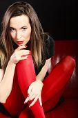 image of pantyhose  - Fashionable woman with long legs in red vivid color pantyhose relaxing on couch indoor on black - JPG
