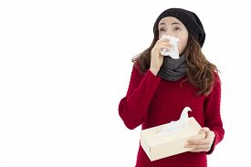 stock photo of tissue box  - Woman sneezing and holding a box of tissue in her hand - JPG