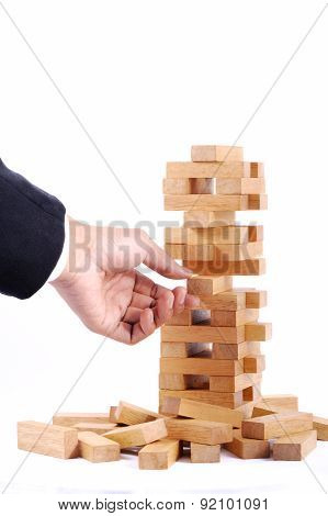 Businessman Playing With The Wood Game (jenga). On White Background
