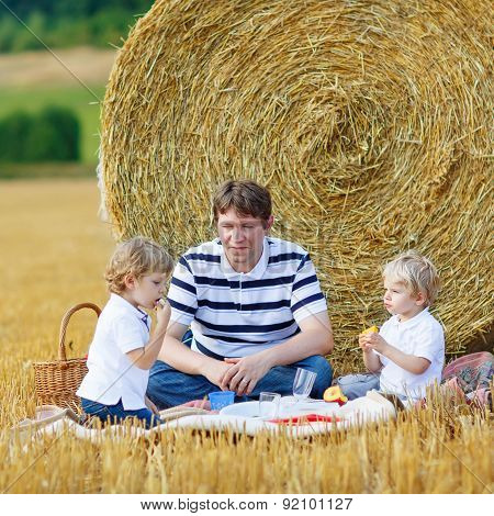 Young Father And Two Little Toddler Boys Having Picnic On Hay Field