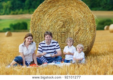 Mother, Father And Two Little Sons Picnicking Together