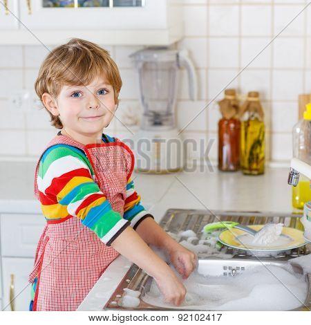 Happy Little Blond Kid Boy Washing Dishes In Domestic Kitchen