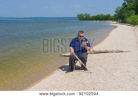 Senior man reading book sitting on a beach of Dnepr river