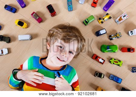 Lovely Blond Kid Boy Playing With Lots Of Toy Cars Indoor