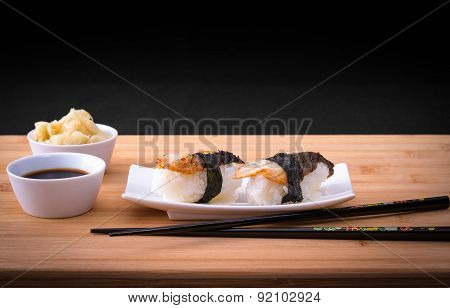 Two Nigiri Sushi Eel With Soy Sauce On Bamboo Table