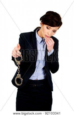Guilty businesswoman holding metal handcuffs.