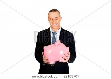 Portrait of cheerful businessman holding piggybank.