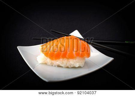 Salmon Nigiri Sushi And Chopstick On Black