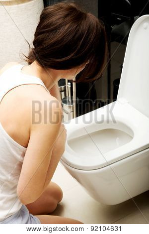 Beautiful adult woman vomiting in toilet.