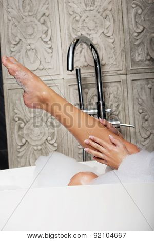 Beautiful bathing woman's leg in bath.