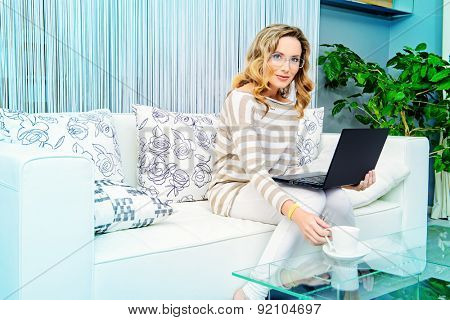 Smiling elegant woman sitting on a sofa with her laptop computer. Home interior, furniture. Lifestyle.