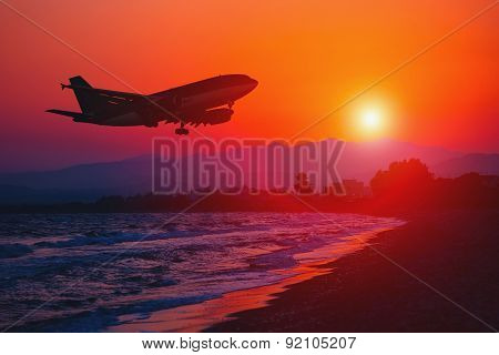 Airplane landing at sunset. Sea and Mountain background.