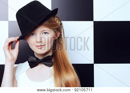 Elegant teen girl wearing white dress, black hat and a bow-tie posing on a background of black and white squares. Youth fashion.