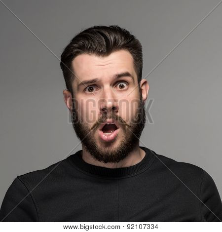 Portrait of a young puzzled businessman with opened mouth