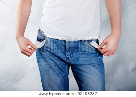 Young poor man with empty pockets.