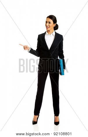 Businesswoman with binder pointing to the left.