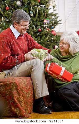 Senior Couple Exchanging Gifts By Christmas Tree