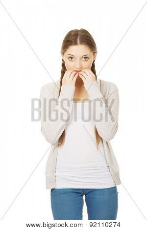 Nervous pensive teenage woman biting nails.