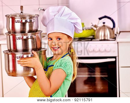Child wearing hat and apron cooking at kitchen.