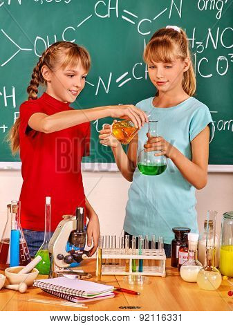 Happy two  female children  holding flask in chemistry class.