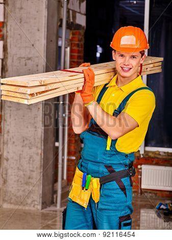 Happy man in builder uniform carry boards indoor.