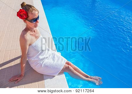 Woman wearing towel red rose with legs in swimming pool