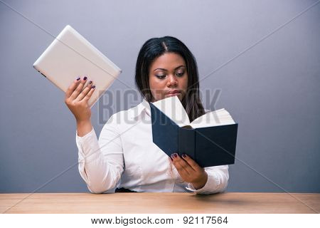 Businesswoman reading paper book and holding e-book over gray background