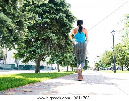 Back view portrait of a fitness woman running outdoors