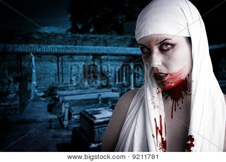 Female Vampire With Blood Stains In A Cemetery. Gothic Image