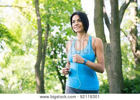Happy sporty woman in headphones running outdoors in park