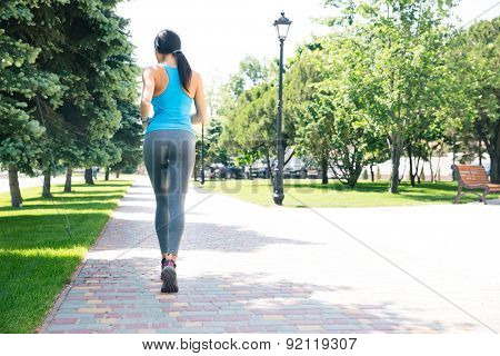 Back view portrait of a sports woman running outdoors