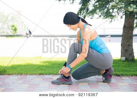Fitness young woman tying her shoelace outdoors