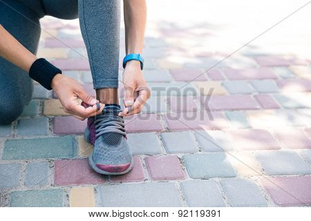 Female hands tying shoelaces outdoors