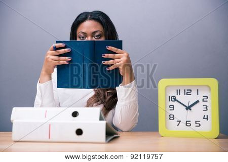 African businesswoman sitting at the table and covering her face with book over gray background. Looking at camera