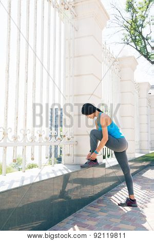 Full length portrait of a young woman runner tying shoelaces