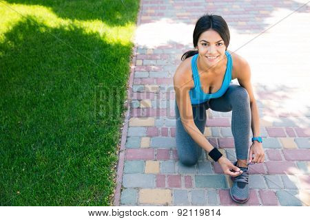 Happy sports woman tying her shoelace outdoors and looking at camera