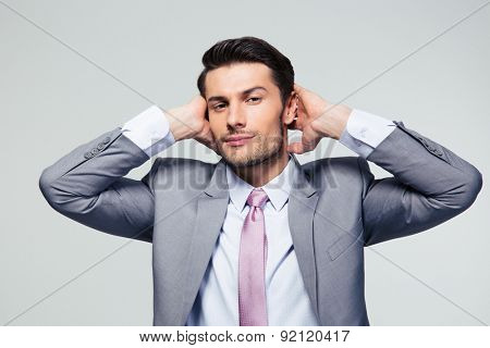 Portrait of a businessman covering his ears over gray background and looking at camera