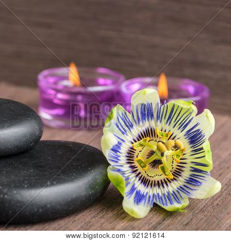 Beautiful Spa Concept Of Passiflora Flower, Black Zen Stones And Candles  On Wooden Background, Clos