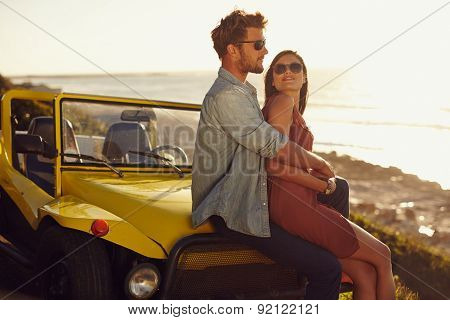 Romantic Young Couple Sitting On The Hood Of Their Car